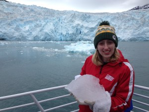 Standing in front of the Aialik Glacier, holding a chunk of it that has melted off.