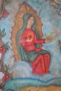 A mural of Mary holding a blessed loaf of bread painted on the wall at Kino Border Initiative