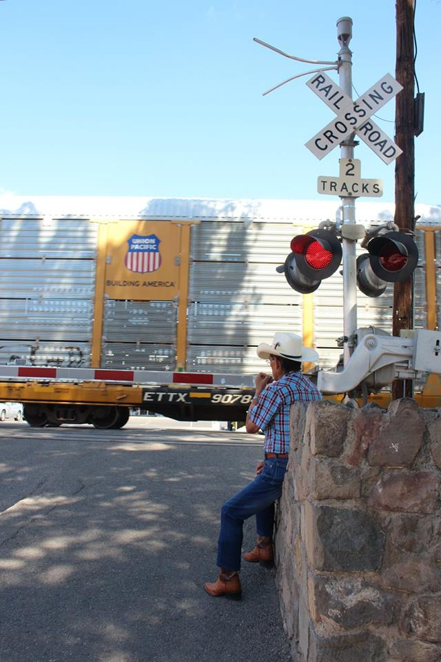 A man sits and watches as a UP train goes right through the middle of downtown Nogales, Sonora.